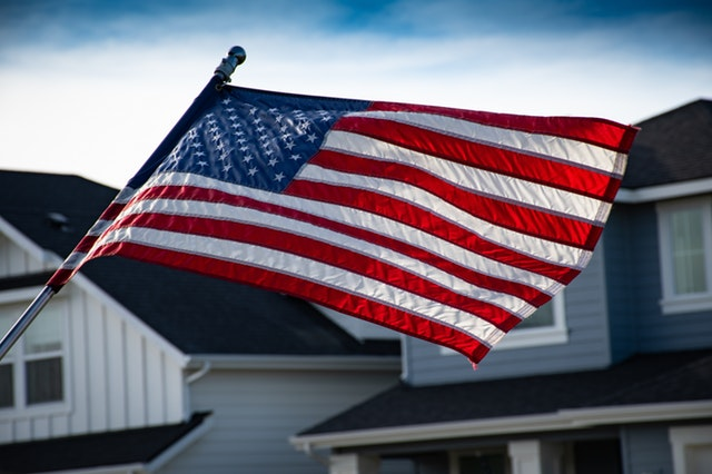 American flag and houses behind