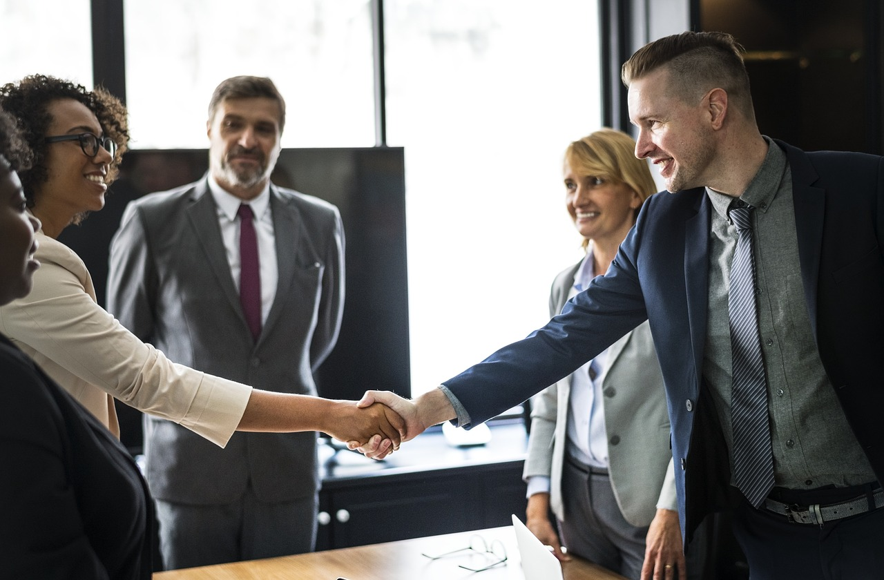 People shaking hands in the office after negotiating a relocation package