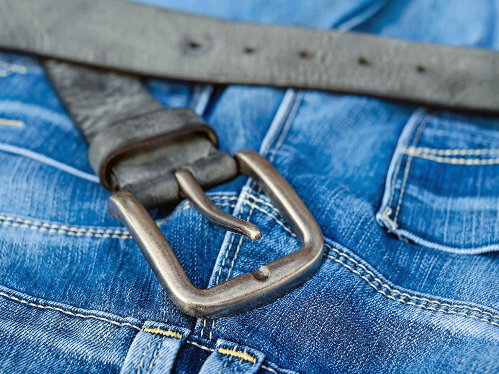 A belt on top of a pair of jeans.