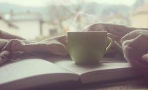 A cup of coffee on an open book.