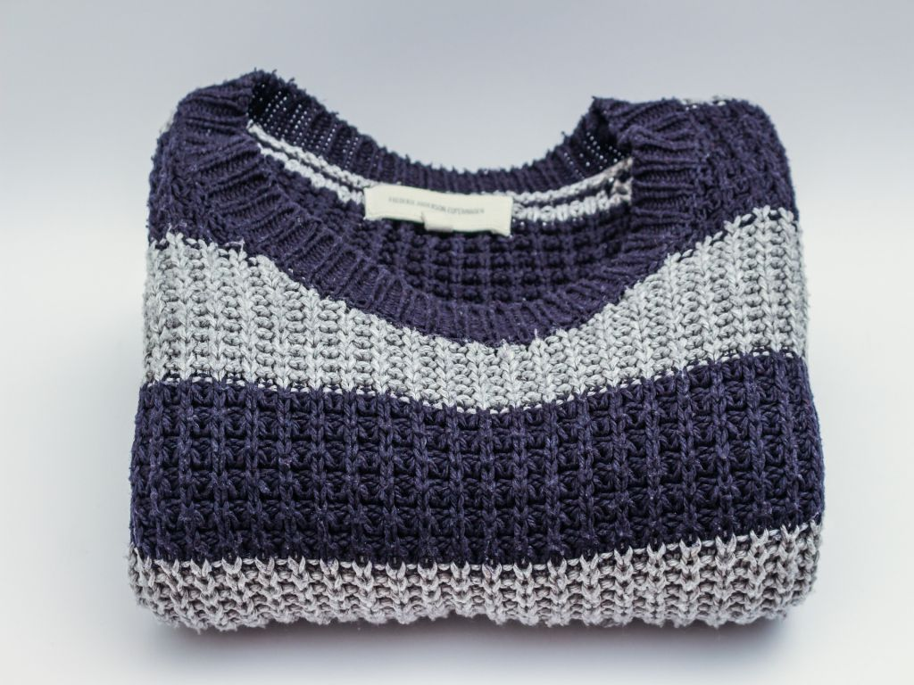 A large sweater folded on a white surface.