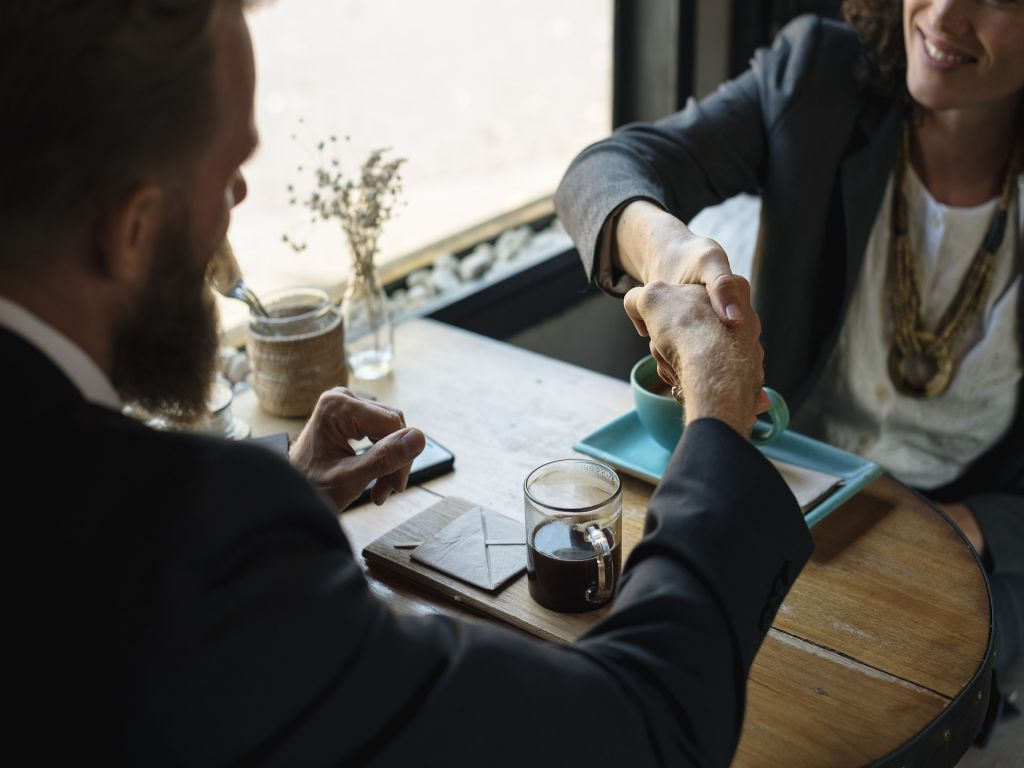 A business meeting over a beverage, with two people shaking hands.