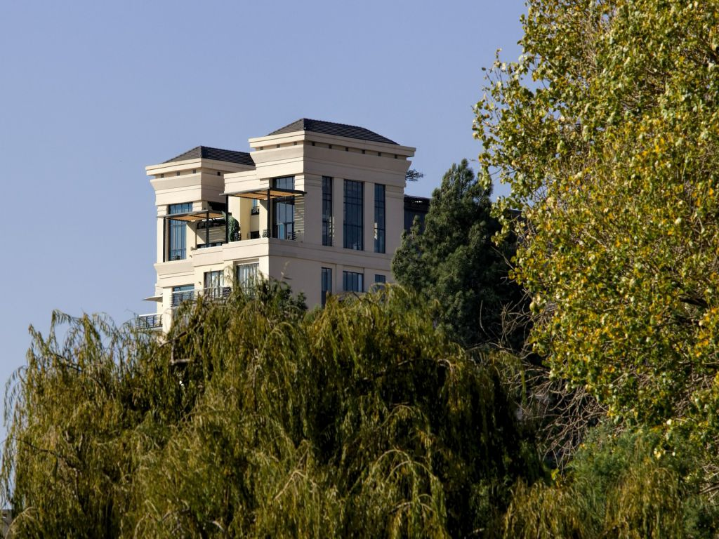 The top floor of a residential building rising above a treeline, representing living in a penthouse.