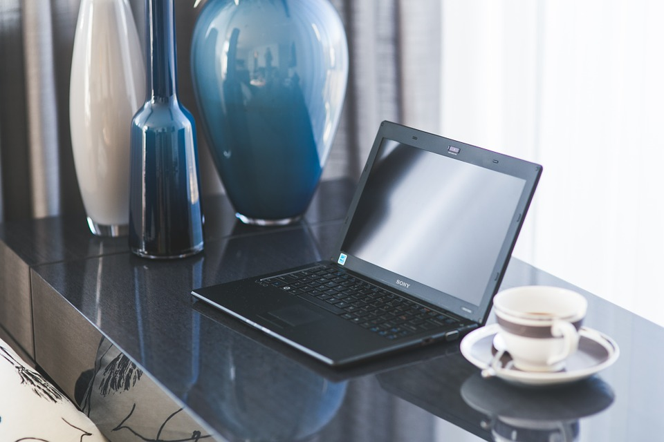 A laptop on a desk next to a lamp and a cup.