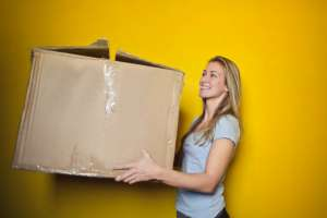 Woman carrying a cardboard box. Smiling.