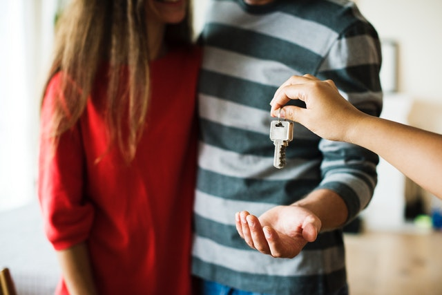 A copule recieving keys to their new home.