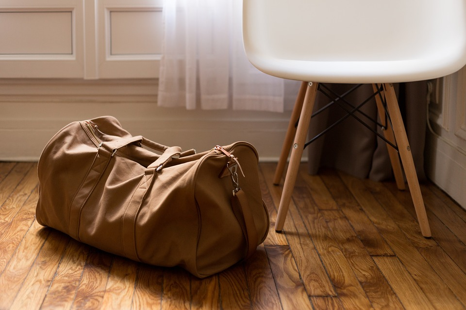 Brown luggage next to a chair on the floor.