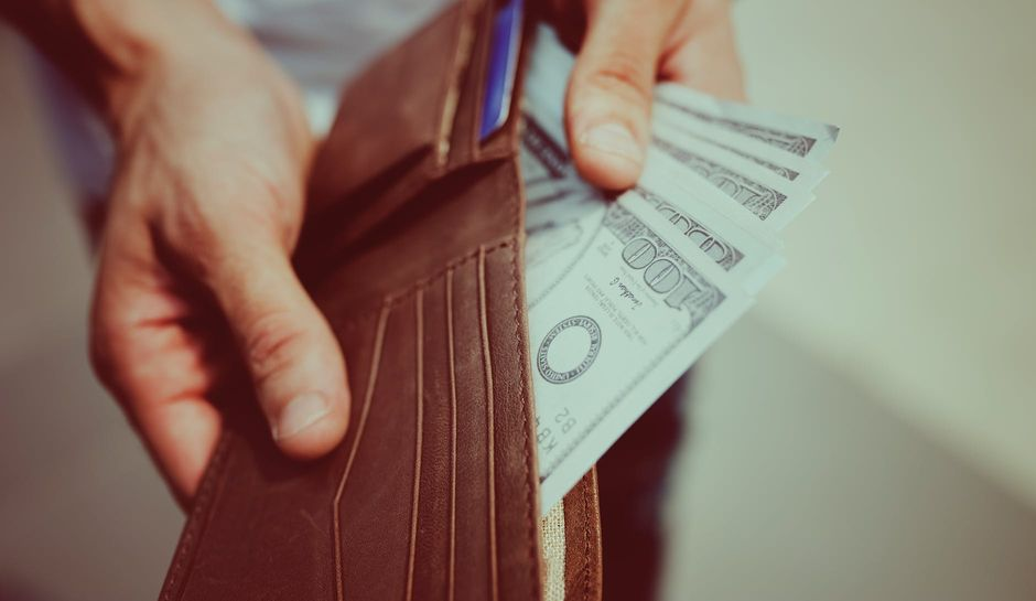 A person taking money out of a wallet.