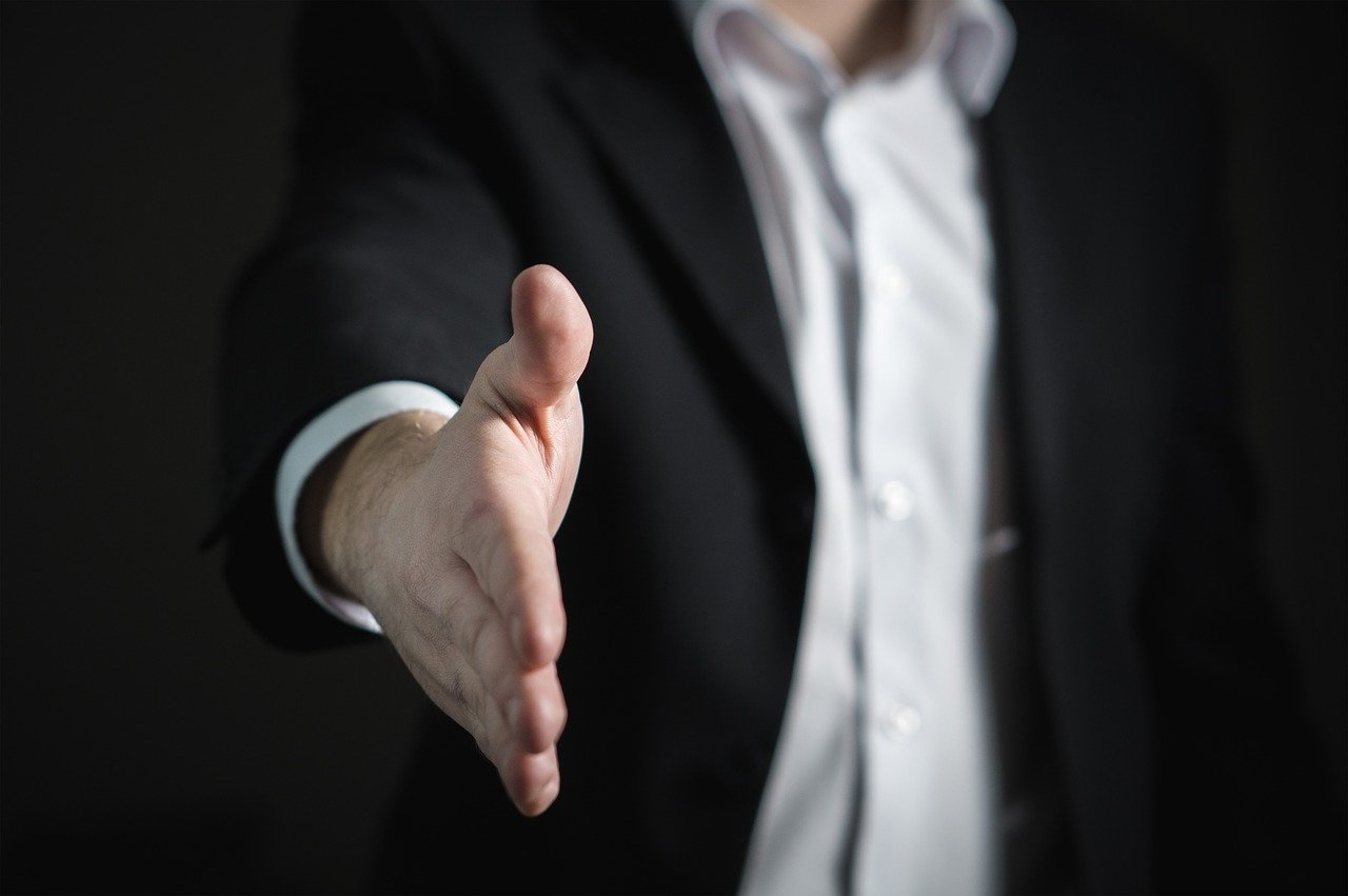 A man in a suit extending his hand for a handshake