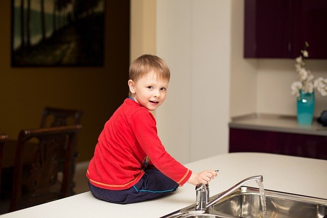Child playing with tap - Include your kids in the unpacking process and avoid similar stations