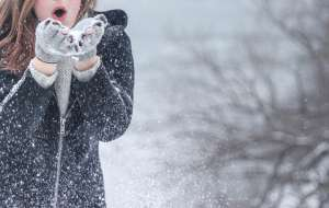 A girl blowing snow off of her hands after she has helped a friend pack for a move