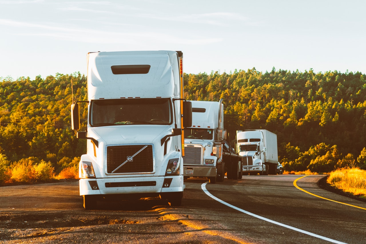 Three trucks on an open road ready for long distance moving