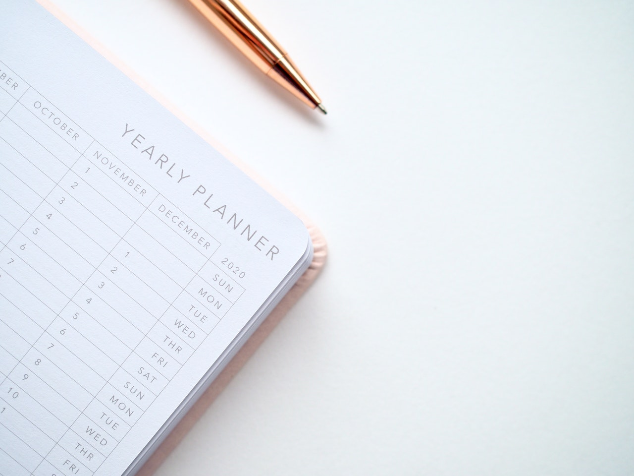 yearly planner and a pen on a white table