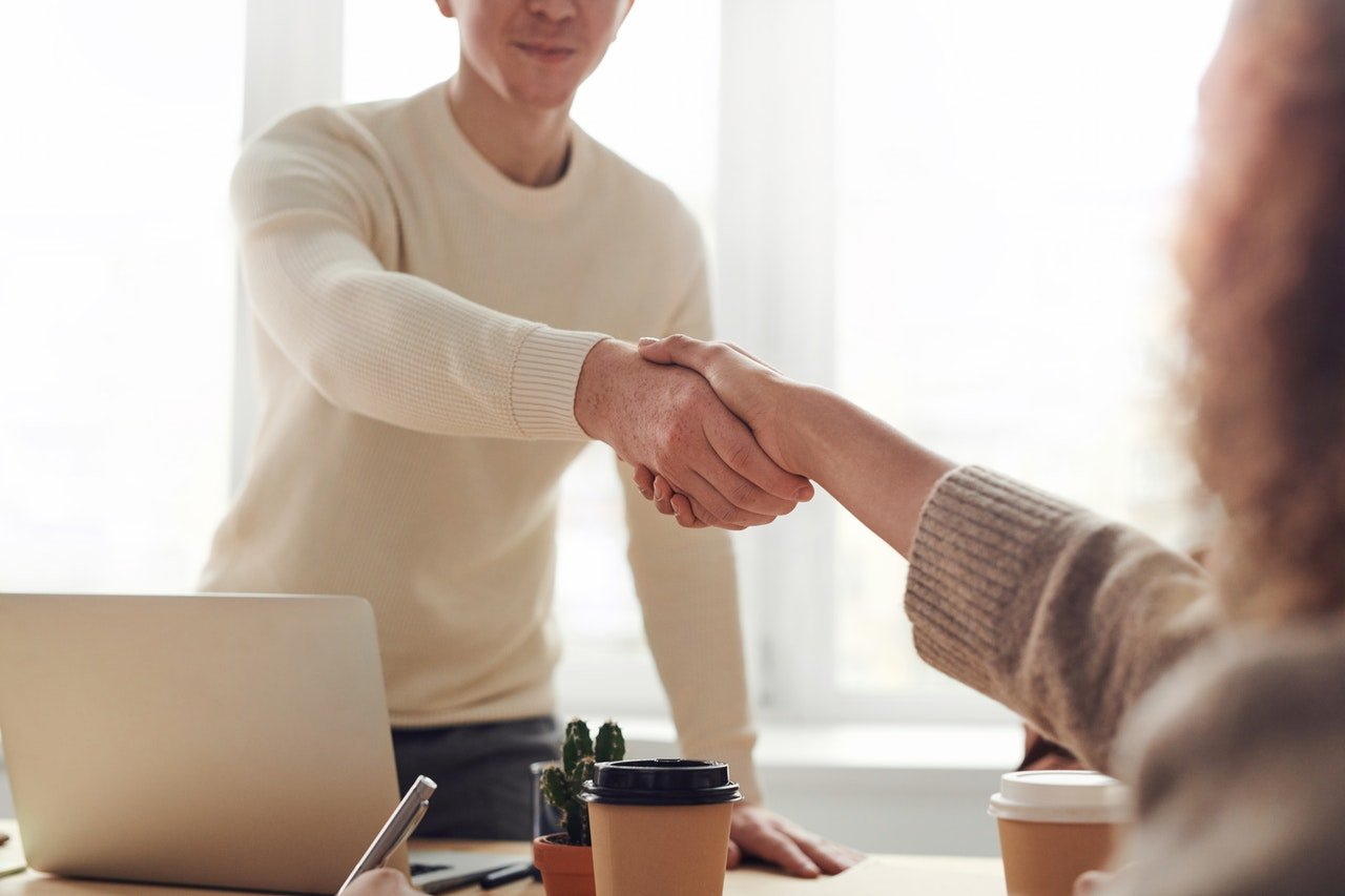 man and woman shaking hands over a table