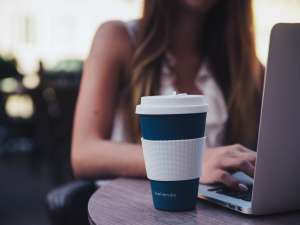 woman working at a laptop with a coffee mug on the side