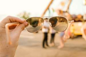 A person holding sunglasses