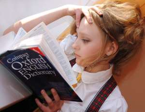 A girl reading the Oxford English Dictonary