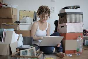 A woman surrounded by boxes browsing on her laptop