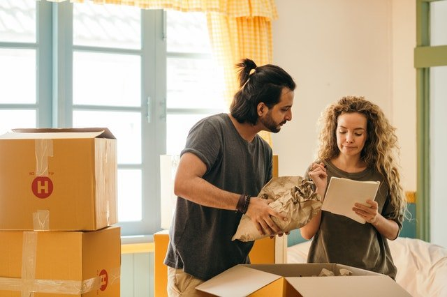 A couple packing moving boxes together