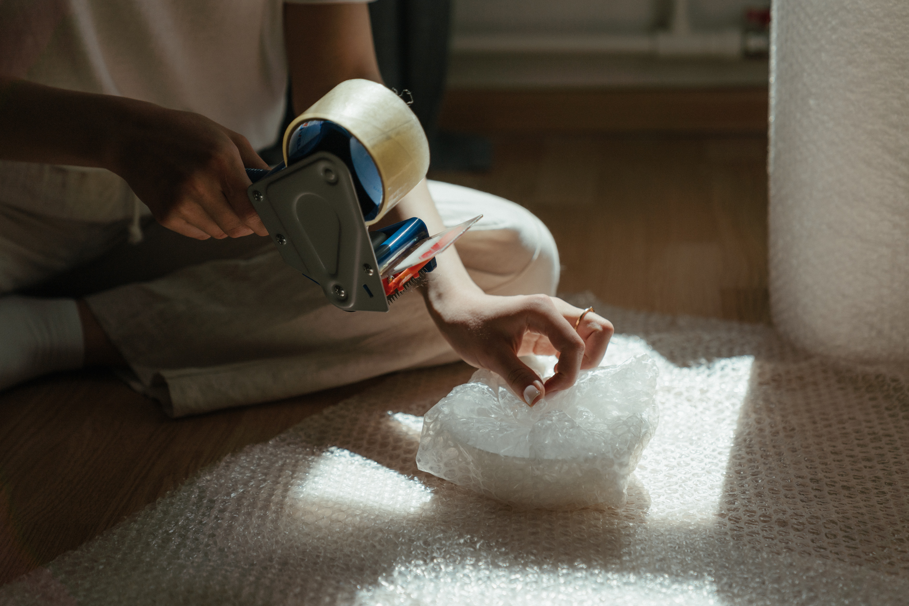 A woman wrapping a bowl in bubble plastic