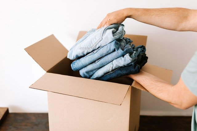 A person packing clothes in moving box