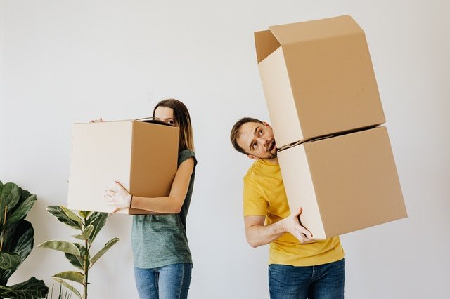 Two people carry boxes