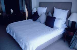 a bed with white sheets as a way to decorate a rental apartment