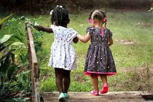 two little girls walking across a wooden bridge as a way to help your child settle in after moving