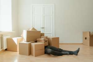 a man laying under a pile of moving boxes