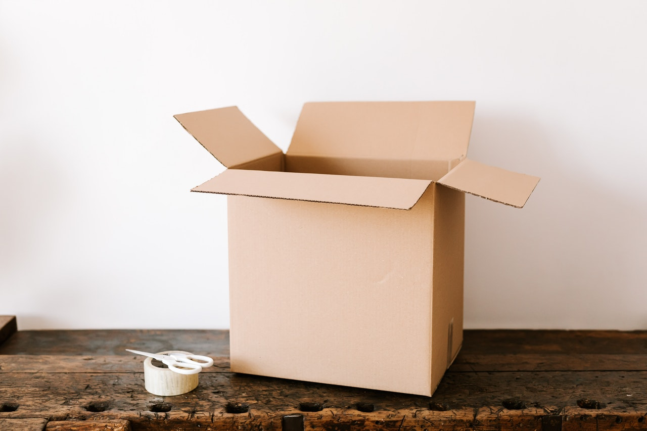 an empty open moving box with a duct tape and a pair of scissors next to it