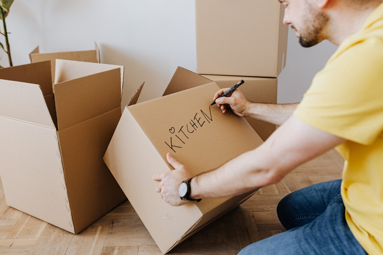 a man in a yellow t-shirt writing the word kitchen on a moving box