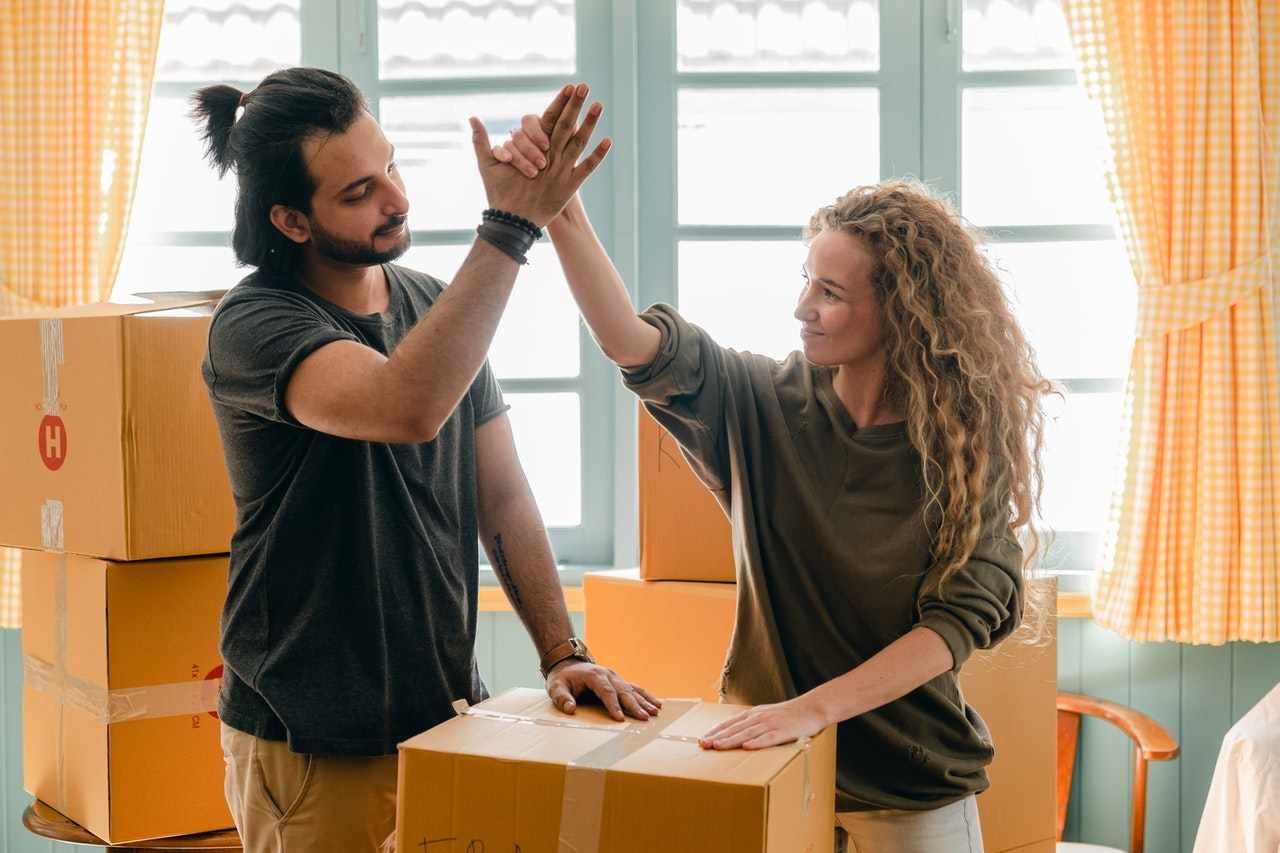 a man and a woman throwing a high five over a moving box