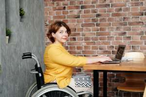 a woman in a wheelchair sitting at a desk