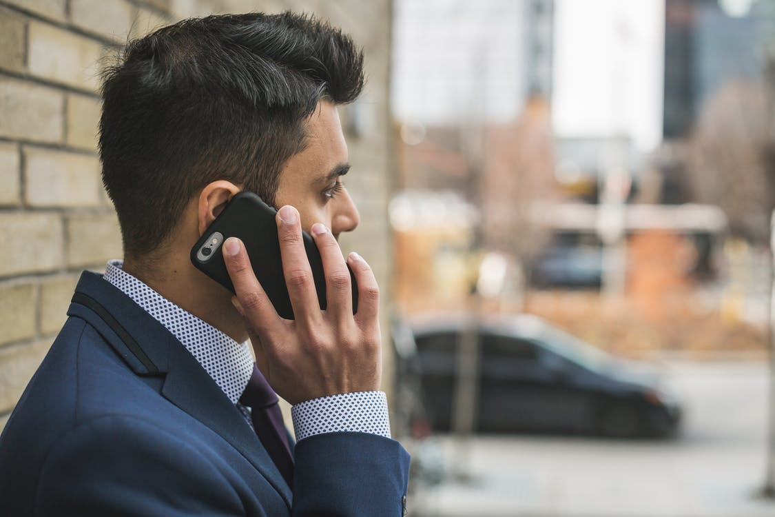 man making a phone call to resolve conflicts with movers
