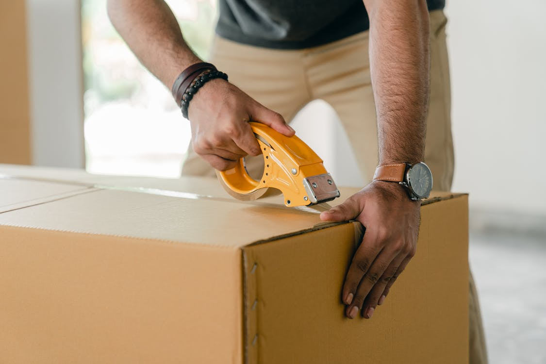 professional mover taping a cardboard box