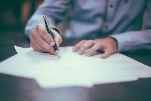 man signing papers - Questions to ask your local movers