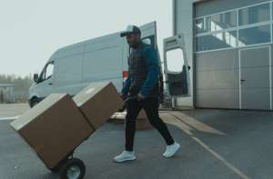 A man using a dolly to move boxes