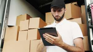 A guy noting down a moving cargo