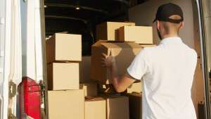 person in a white shirt and black hat, packing cardboard boxes in a moving van