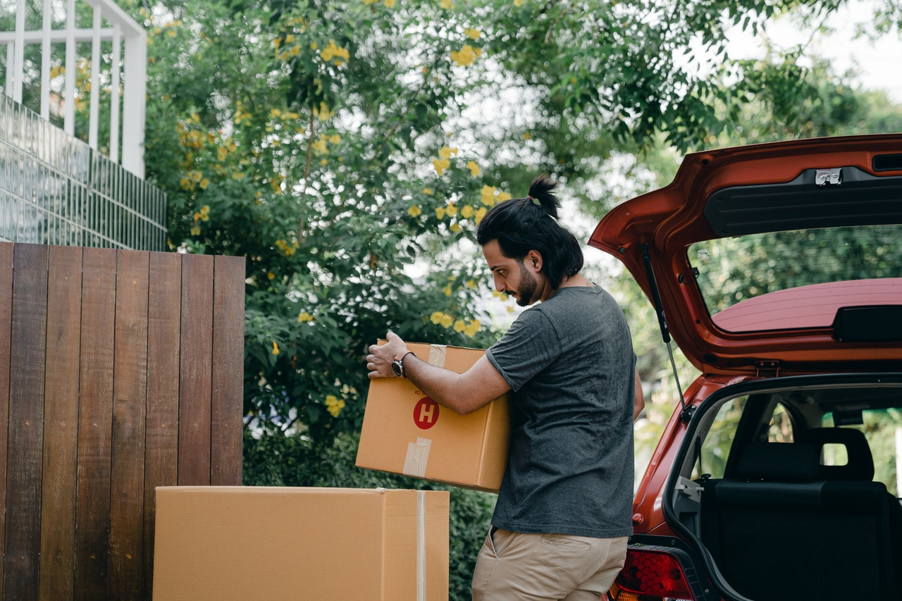 man packing boxes in a car