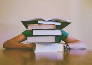 A person sleeping behind a pile of books
