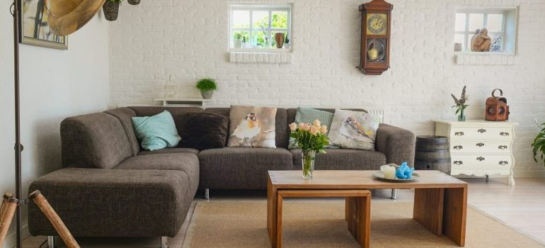 a living room with furniture, sofa, table, pictures on the walls